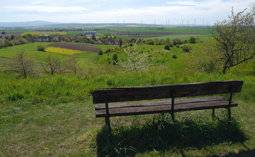Eine Landschaftsaufnahme. Das Foto wurde hinter einer Bank, die aufn einem Berg oberhalb von einem Dorf steht, aufgenommen. Im Hintergrund sieht man den Harz und Felder und Windkraftanlagen.