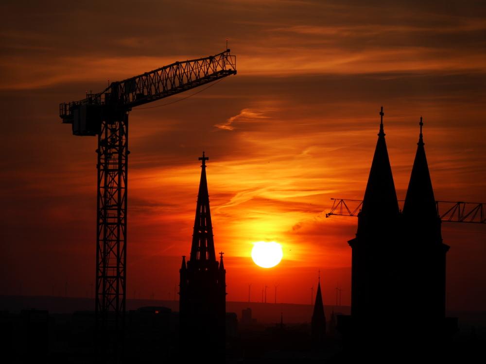 Das Foto zeigt einen dramtischen Sonnenuntergang, die Sonne geht zwischen den Türmen von zwei Kirchen unter, man sieht auch einen nahezu vollständigen Baustellenkran und den Ausleger von einem weiteren Kran. Im Hintergrund sind auf den Bergen Windräder erkennbar. Die Sonne steht relativ nahe am Horizont, dadurch ist das ganze Bild von gelb/orangenem Licht geprägt und die Kirchen und Kräme sind Silouetten.