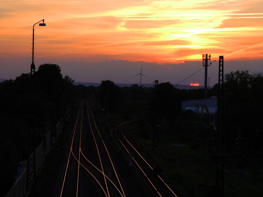 Eine Landschaftsaufnahme bei Sonnenuntergang, die Sonne hat den Himmel orange eingefärbt. Das Bild zeigt unten die Gleise von zwei Bahnstrecken, eine doppelgleisige führt geradeaus durch das Bild, eine eingleisige Strecke biegt nach Rechts ab. Aufden durch den Zugverkehr blankenn Schienen spiegelt sich die Sonne was ein wenig danach aussieht, als würden die Schienen leuchten. Im Hintergrund sind Windräder erkennbar.
