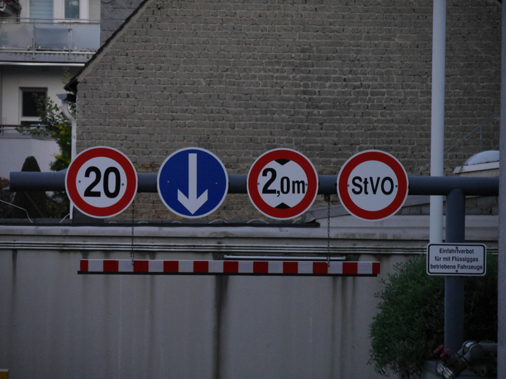 """Die Einfahrt zu einer Tiefgarage, an einem dicken Rohr sind über der Einfahrt 4 Verkehrsschilder angebracht, von links nach Rechts: Höchstgeschwindigkit 20 km/h, dann ein blaues, rundes Pfeilschild nach unten, dann maximale Höhe 2m und dann ein rundes Verbotsschild, in dem """"StVO"""" steht. Rechts ist dann noch ein Hinweisschild """"Einfahrverbot fü rmit Flüssiggas betriebene Fahrzeuge"""""""