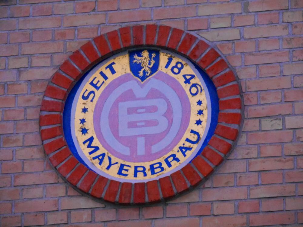 """Ein altes, rundes und auf einer Backsteinmauer aufgemaltes und in Backsteinen eingefasstes Schild """"MAYERBRÄU SEIT 1846"""" mit dem Logo der Brauerei"""