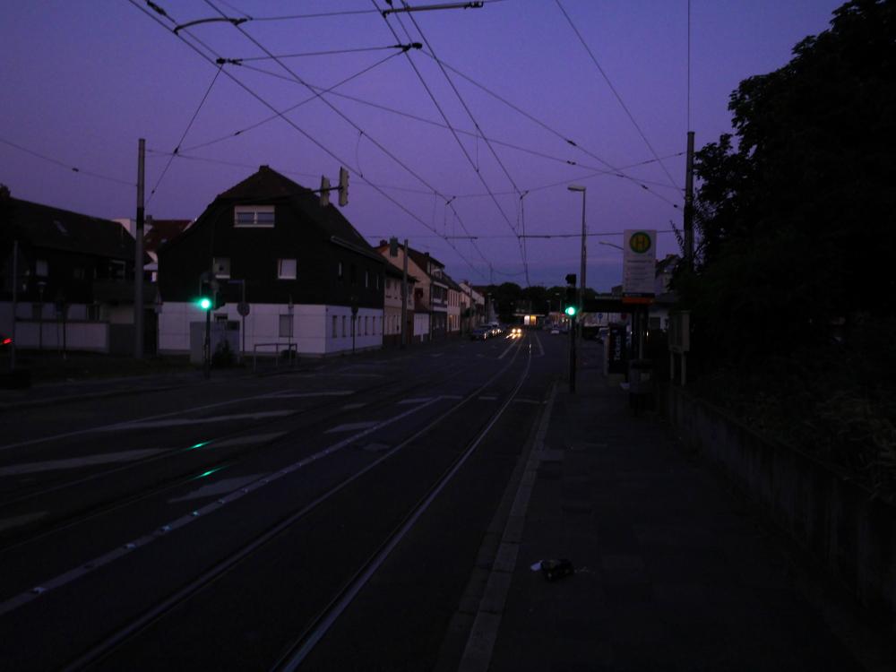 Eine Straßenszene am späten abend, es dämmert schon, die Straßenlaternen sind aber noch aus. Man sieht Straßenbahngleise auf der Straße, rechts ist eine Haltestele und davor eine Ampelanlage, weiter hinten auf der Straße sieht man ein Auto fahren
