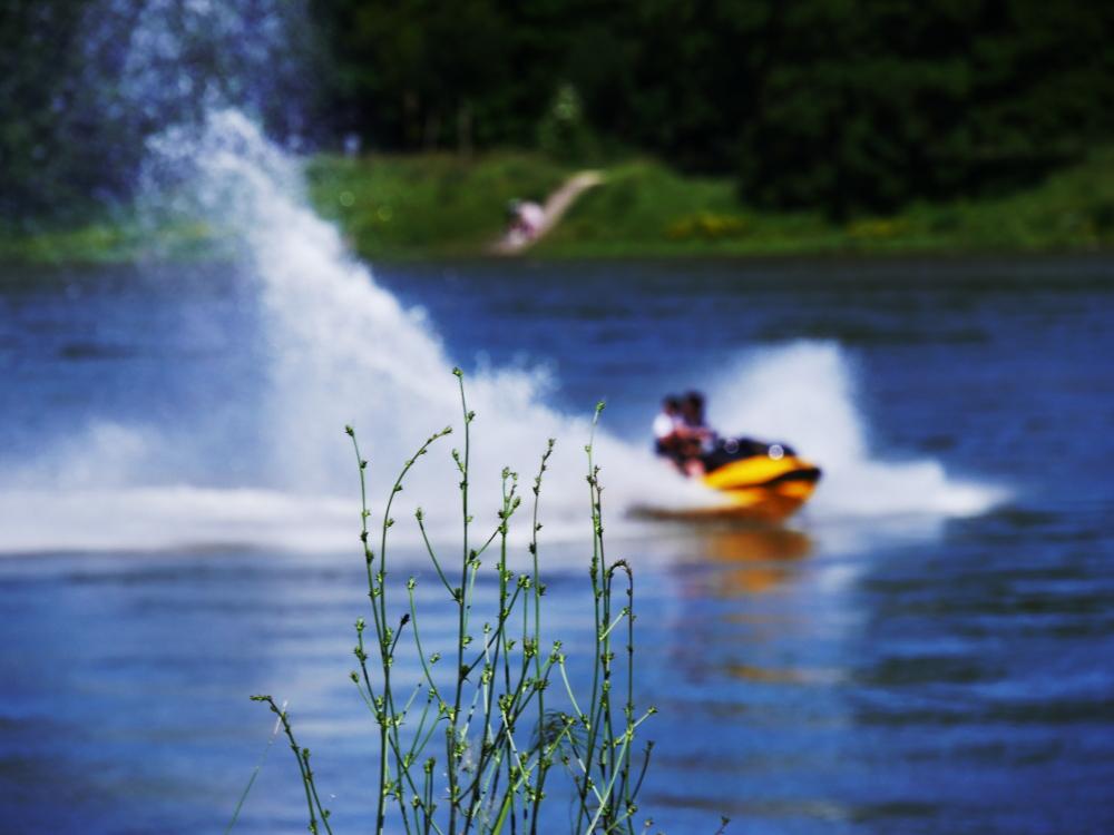 Das Foto zeigt eine experimentelle Aufnahme an einem Fluß (Rhein). Scharf abgebildet wird ein Strauch etwa in der Bildmitte. Der Rest vom Bild ist unscharf, man kann in der Unschärfe aber einen Jetski/Wassermotorrad erkennen, welches das Wasser spritzen lässt und auf dem zwei Menschen sitzen (die Menschen sind nicht erkennbar). Das Ufer auf der anderen Seite ist auch erkennbar und unscharf, man sieht da verwaschene Wege und Menschen.