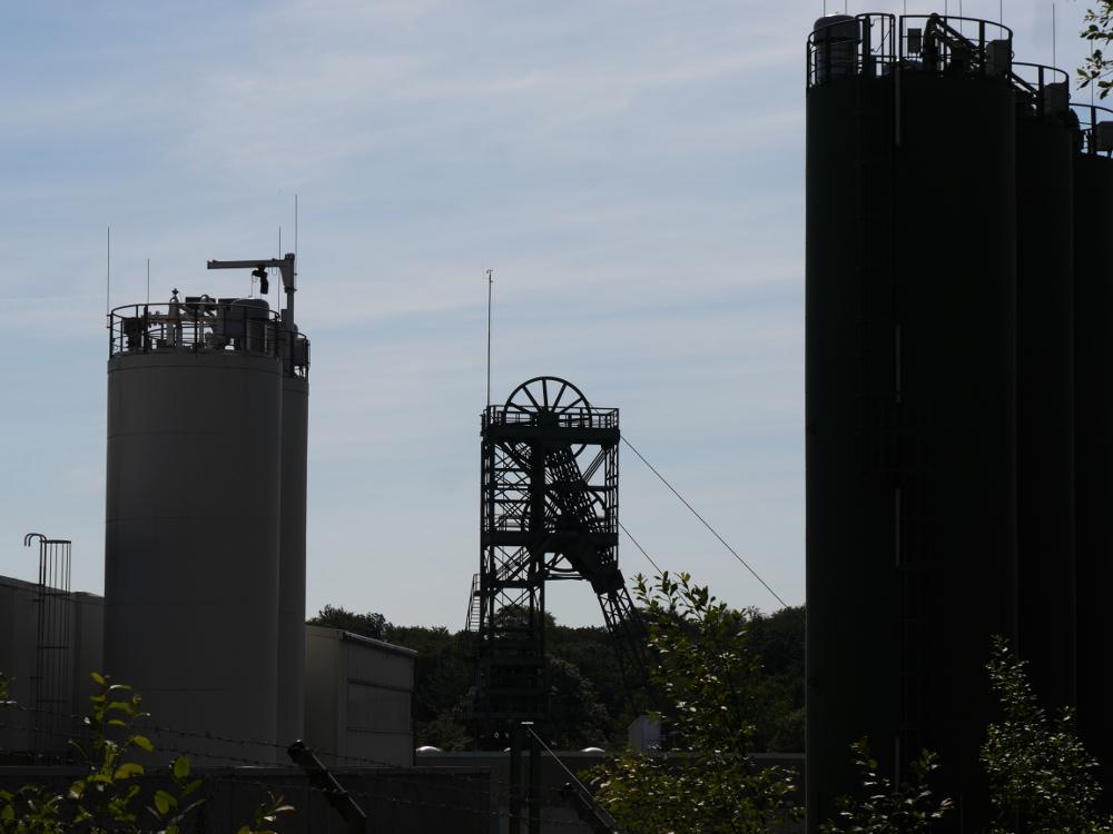 Das Foto zeigt das zweirädigere Fördergerüst der Schachtanlage Asse II in der Mitte, rechts und LInks wird das Bild durch große Metallsilos begrenzt.