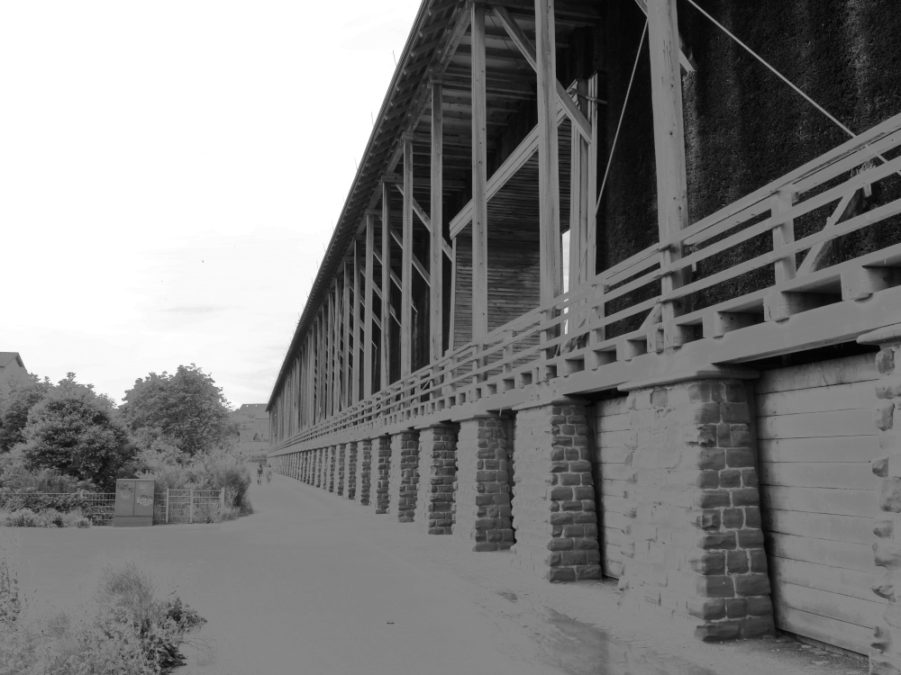 Das Bild zeigt ein schwarz-weiß-Foto von einem Gradierwerk, das Gradierwerk zieht sich rechts praktsich durch das ganze Bild zum Horizont. Am Gradierwerk entlang geht ein Weg, auf dem man Menschen erkennen kann, daneben sind Bäume und Büsche. Durch eine Kontrastbearbeitung wirkt das Bild verfremdet und befremdlich.