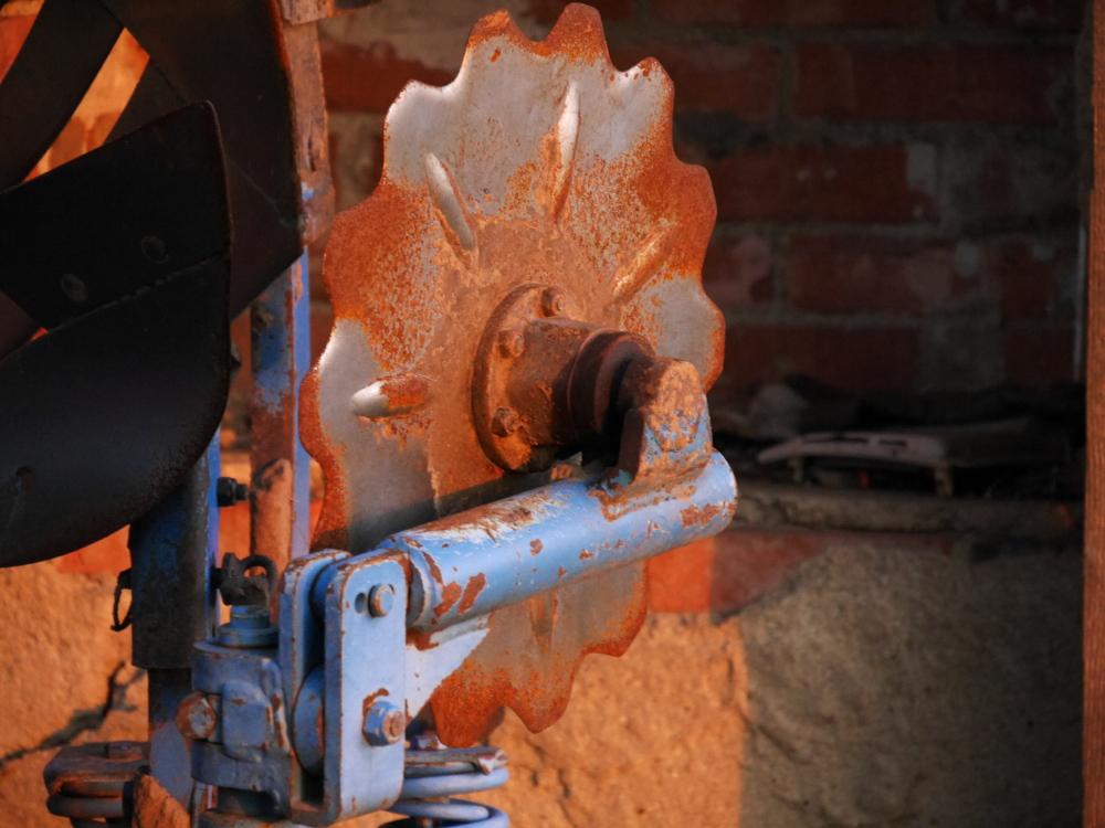 Ds Foto zeigt einen Teil eines alten lndwirtschaftlichen Geräts, hierbei als Detail ein Metallrad, welches schon angerostet ist und an einem blau lackierten, ebenfalls angerosteten Halter hängt.