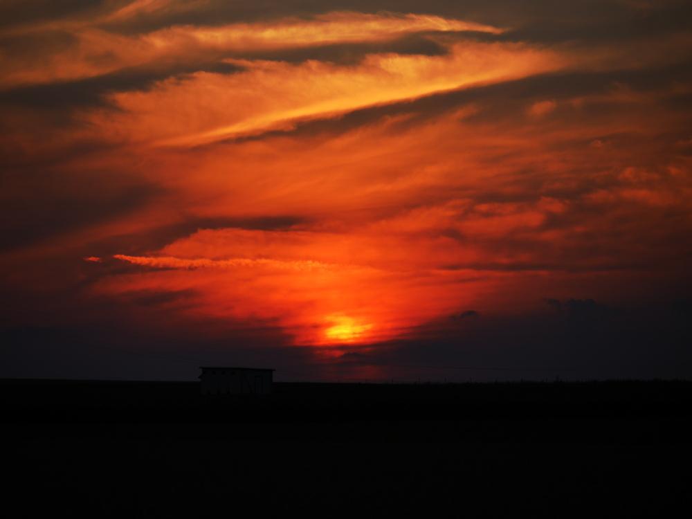 Das Foto zeigt einen dramtischen Sonnenuntergang. Die Sonne ist schon kurz über dem Horizont und leicht hinter Wolken verborgen, alles ist Orange-Gelb und durch die Wolken sehr weich. Man kann die Silouette einer Hütte erkennen.