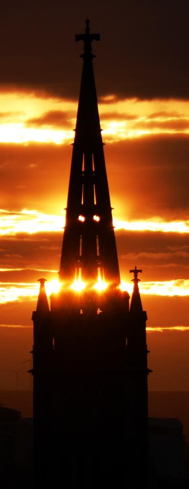 Das Bild ist schwierig zu beschreiben, ich versuche es mal: Man sieht einen Kirchturm vor einem Sonnenuntergang. Der Kirchturm ist dadurch nur als dunkle Silouettte erkkenbar und zusätzlich sind noch viele Wolken am Himmel, so das man von der Sonne nur noch orangene Streifen sieht und erahnen kann, das die Sonne direkt hinter dem Kirchturm ist. Die Kirchturmspitze ist aber nicht massiv, so das die Sonne durchscheinen kann, was so aussieht, als gebe es da im Kirchturm glühende Lichter und es erweckt ein wenig den Eindruck, der Kirchturm hätte eine Aura, wodurch es leicht mysteriös aussieht.