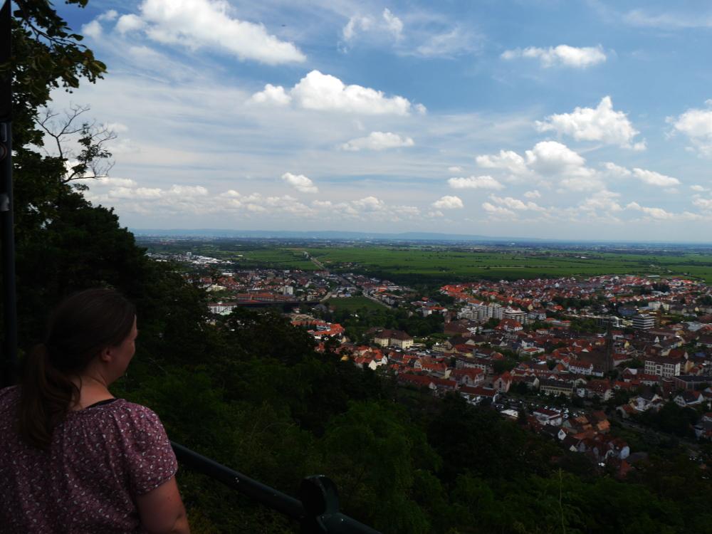 Eine Landschaftsaufnahme hoch über der Stadt Bad Dürkheim. Rechts steht im vorderen Bildteil eine Fau und schaut nach unten auf die Stadt. Hinter der Stadt geht es in der Rheinebene weiter, man sieht Felder und kann am Horizont weitere Städte erahnen.