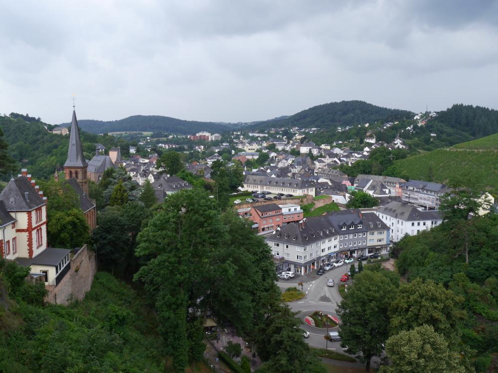 Ein Landschaftsfoto von Saarburg. Das Foto ist von oberhalb der Stadt aufgenommen, man sieht die Stadt zwischen den Bergen, links Teile einer Kirchenanlage, unten im taal die Häuser und eine Straße.