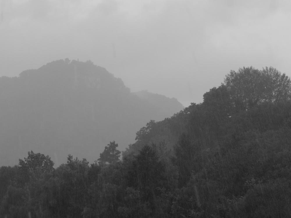 Ein schwarz-weiß-Foto von einer Landschaft im Nebel und Regen, man sieht hintereinander zwei Berge wobei der zweite Berg im Nebel verschwindet. Beide Berge sind bewaldet.