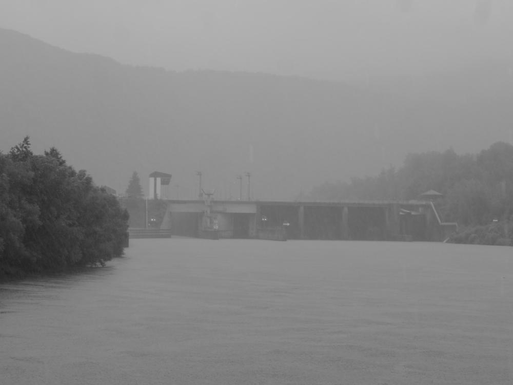 Ein schwarz-weiß-Foto einer LAndschaft mit Schleuse an der Saar. Es ist schlechtes Wetter mit Nebel und Regen und die Schleuse versinkt im Nebel.