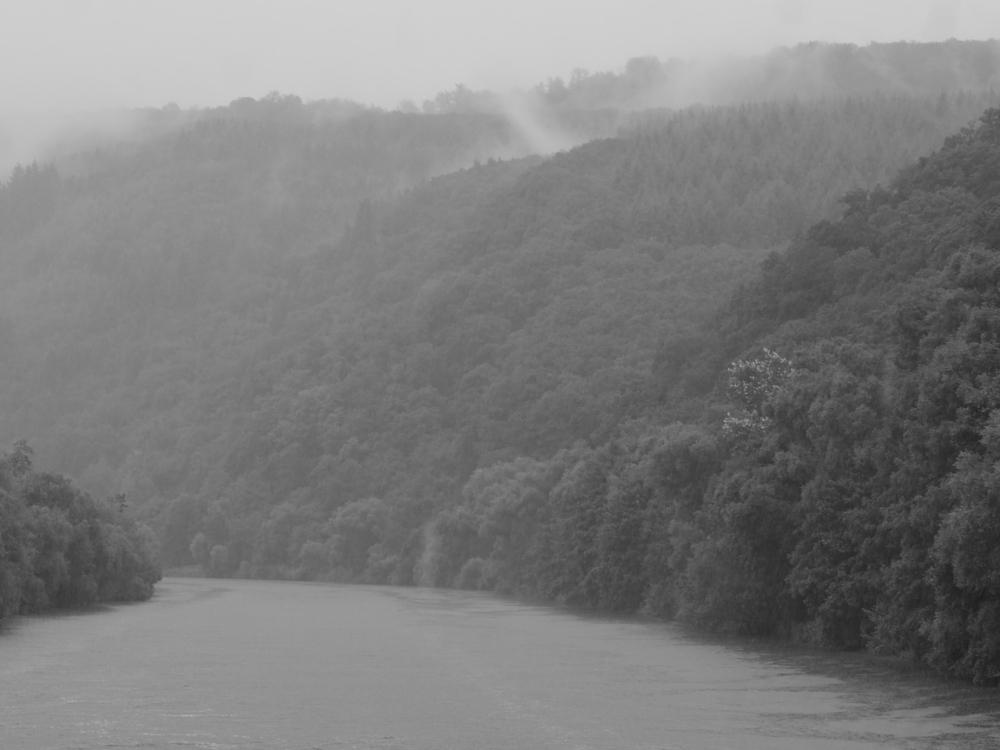 Das schwarz-weiß-Foto zegt eine Landschaftsaufnahme an der Saar. Unten der Fluß, darüber bewaldete Hänge. Es ist neblig und regnet, man kann die Nebelschwaden an den Hängen erkennen.