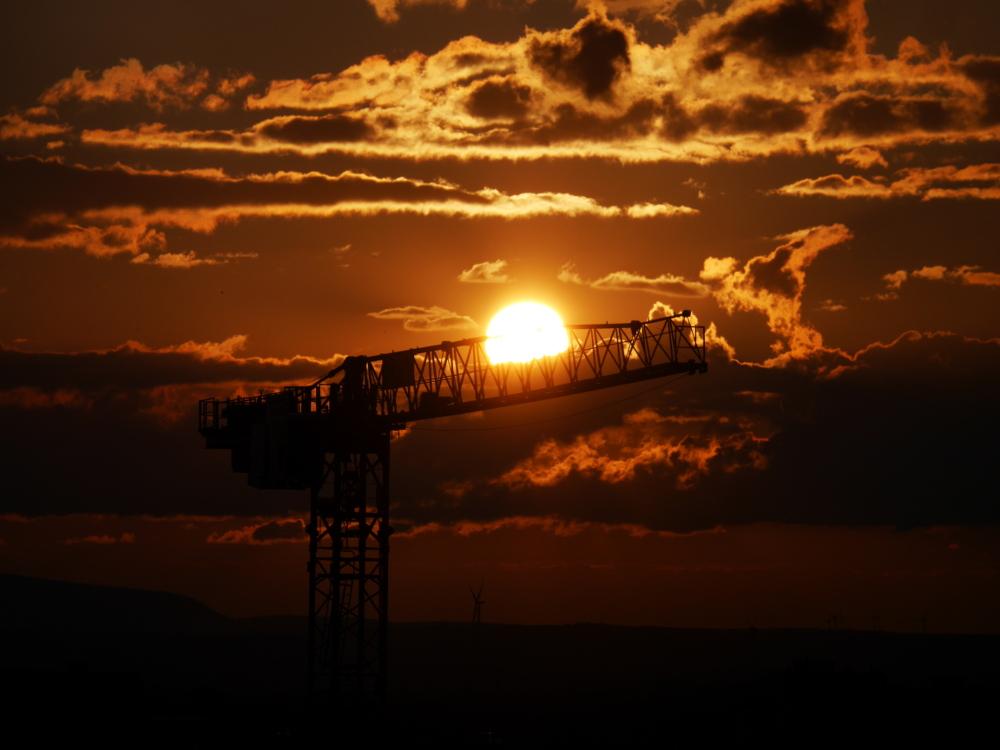 Das Foto zeigt einen dramatischen Sonnenuntergang hinte reinem Baustellenkran. Die Sonne steht gerade auf der Höhe des Kranauslegers, am Himmel sind wolken und es ist alles rot-orange eingefärbt.