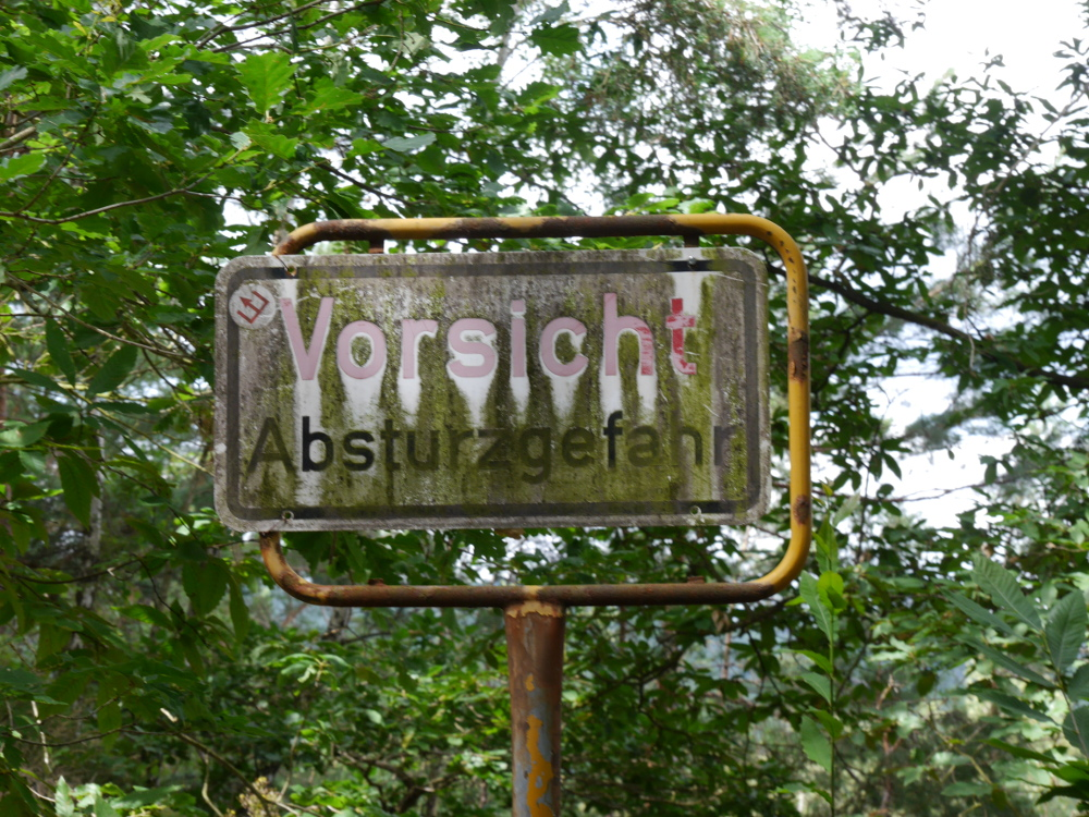 """Ein altes, völlig verrostetes Blechschild mit der Aufschrift """"Vorsicht Absturzgefahr"""" im Wald, Das Schild passt nicht zum """"Rahmen und ist daher mehr provisorisch so festgeschraubt, das es teilweise über den Rahmen hinausgeht. Zusätzlich zum Rost ist das Schuld auch noch verdreckt."""