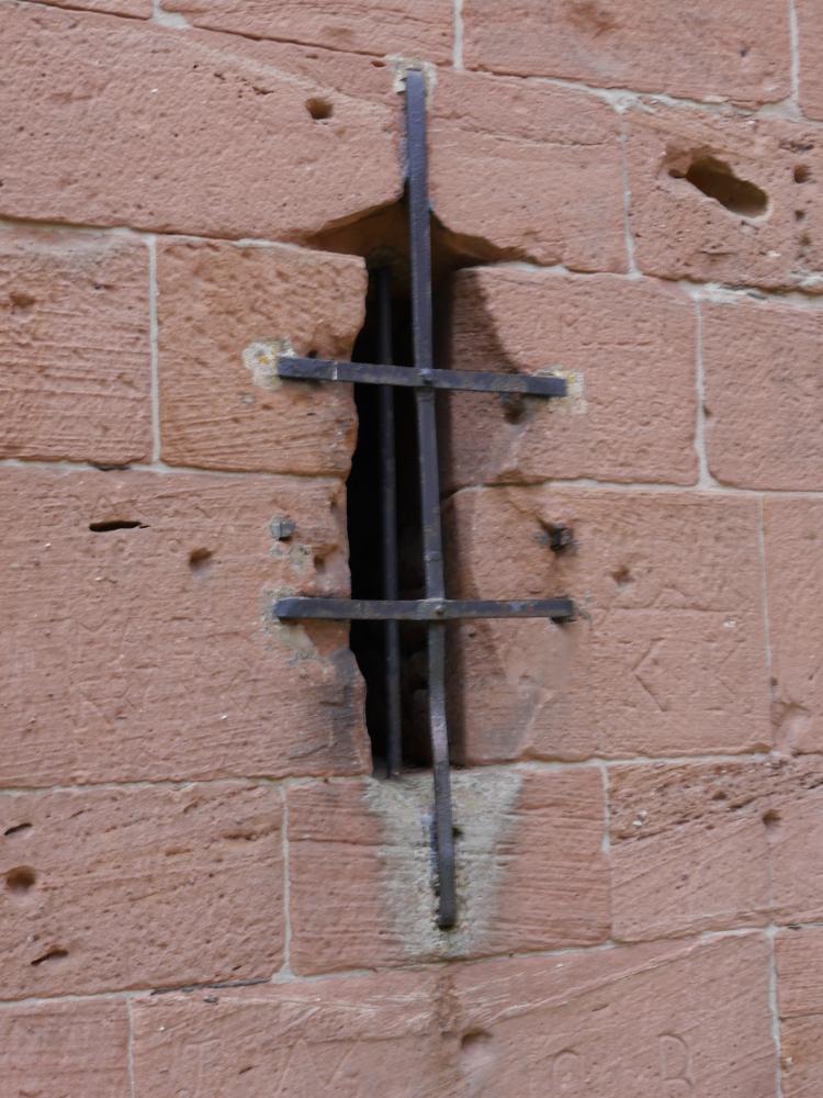 Detailaufnahme einer kleinen, durch Stahlstreifen vergitterten Öffnung in der Turmmauer der Klosterruine Limburg