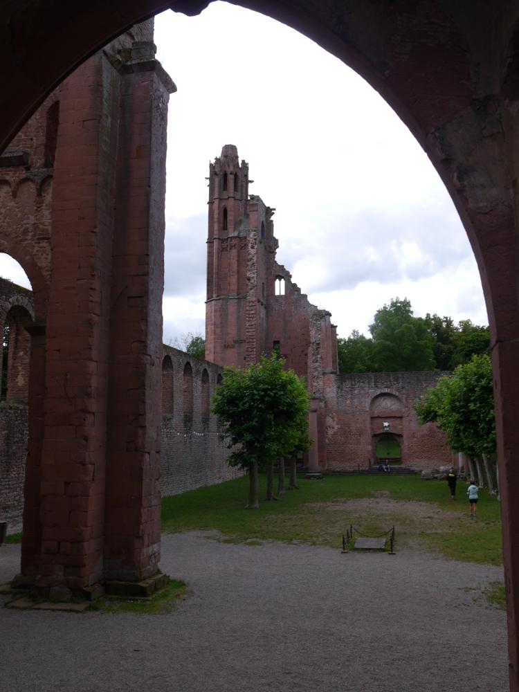"""Eine Innenaufnahme im """"Hof"""" der Klosterruine Limburg bei Bad Dürkheim. Der Blick geht durch einen Rundbogen und man kann hinten die Reste eines Turms erkennen. Im Klosterhof (das Dach fehlt) stehen Bäume."""