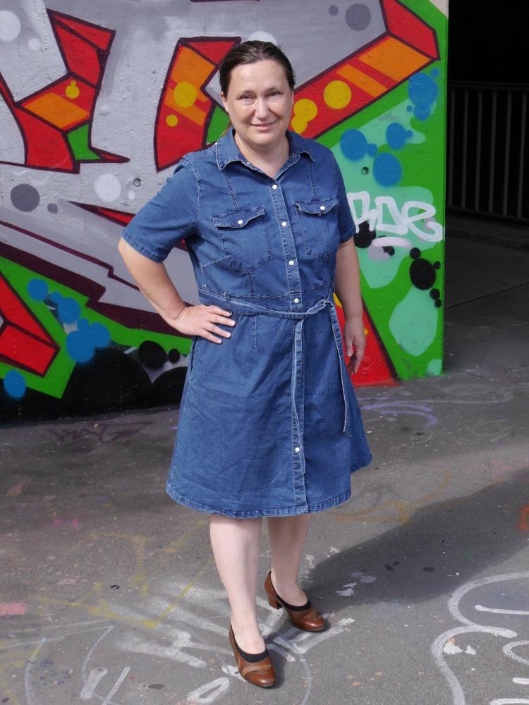 Eine Frau in einem blauen Jeanskleid und braunen Pumps steht vor einer mit Graffiti bemalten Wand und schaut lächelnd in Richtung der Kamera