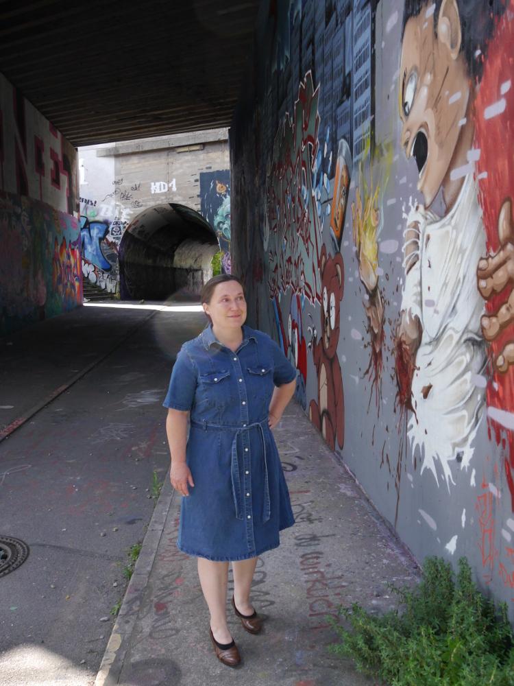 Eine Frau in einem blauen Jeanskleid und mit braunen Pumps steht in einem Fußgängertunnel, dessen Wände mit Graffiti bemalt sind. Etwa auf höhe der Frau beginnt eine Graffiti-Straßenszene, die sich durch den ganzen Tunnel zieht. Im Hintergrund kann man einen zweiten, ebenfalls mit Graffiti bemalten Tunnel erkennen.