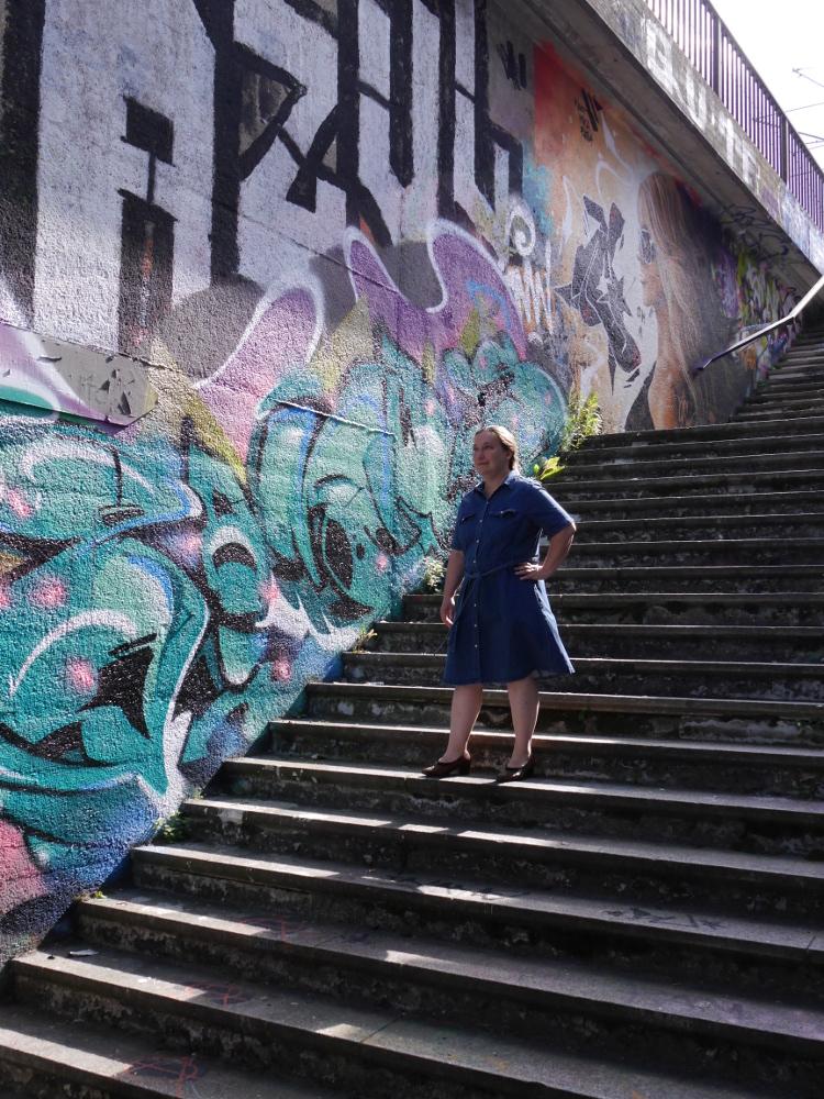 Eine Frau steht in einem blauen Jeanskleid und braunen Pumps auf einer Treppe, die von einer Unterführung zur Straßenebene führt. Die sichtbare Wand des Treppenaufgangs ist mit Graffiti bemalt.