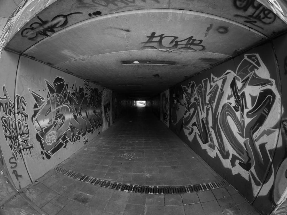Das schwarz-weiß-Foto von einem Fußgängertunnel, beide Wände sind mit verschiedenen Graffitis bemalt, man sieht weiter hinten das Licht am Tunnelausgang