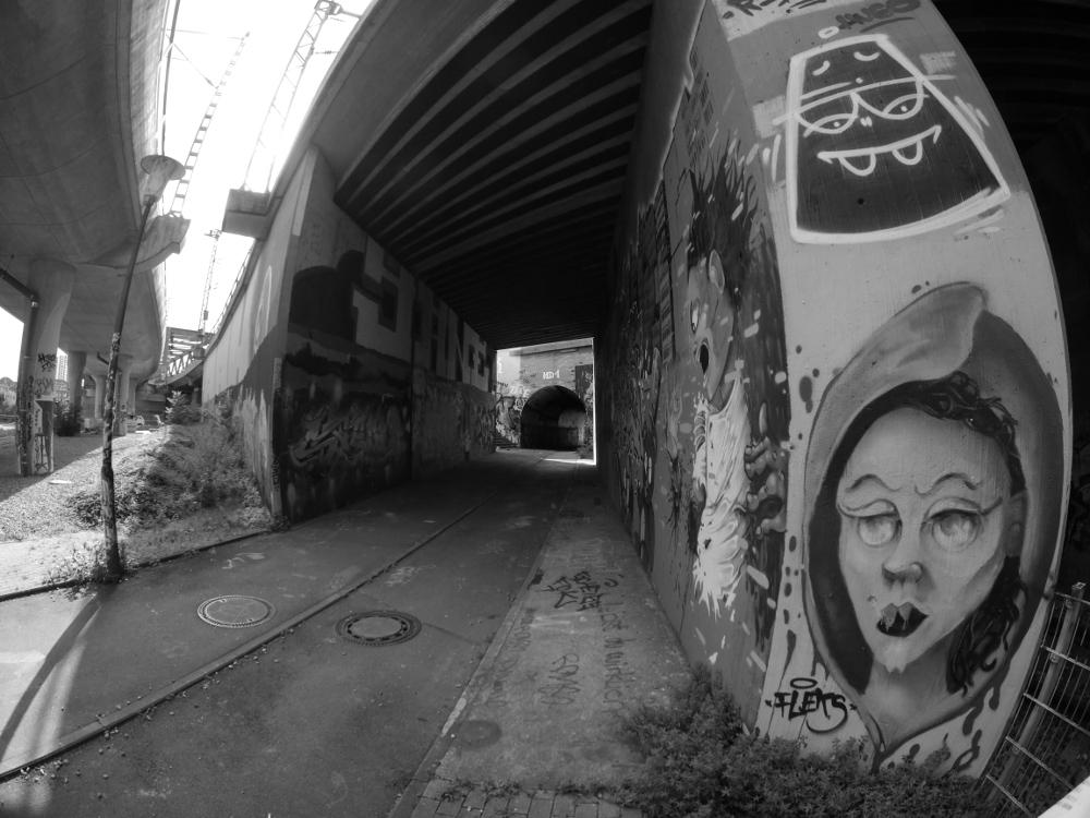 Das schwarz-weiß-Foto zeigt Fußgängerwege unter Eisenbahnbrücken, die Brückenpfleiler/Wände sind mit verschiedenen Graffiti bemalt. Am Pfeiler rechts sieht man ein in Richtung der Kamera blickendes weibliches, aber doch irgendwie fremdartiges Gesicht