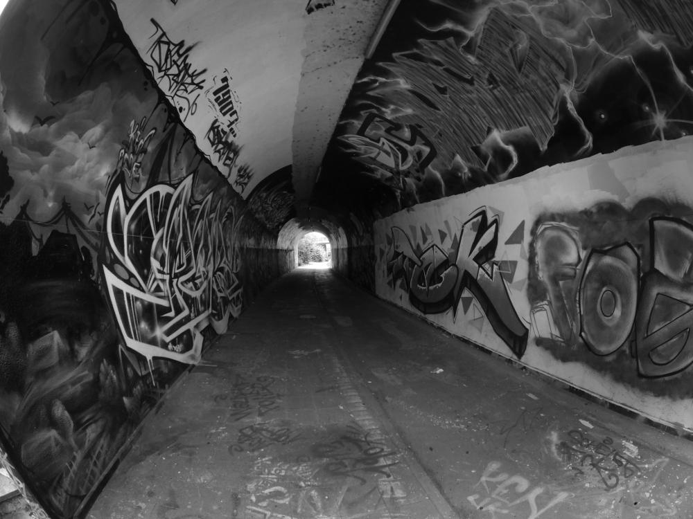 Das schwarz-weiß-Foto zeigt einen gewölbten und in einem leichten rechts-bogen verlaufenden Fußgängertunnel, die Wände und die gewöble Decke sowie der Fußweg sind mit verschiedenen Graffiti bemalt