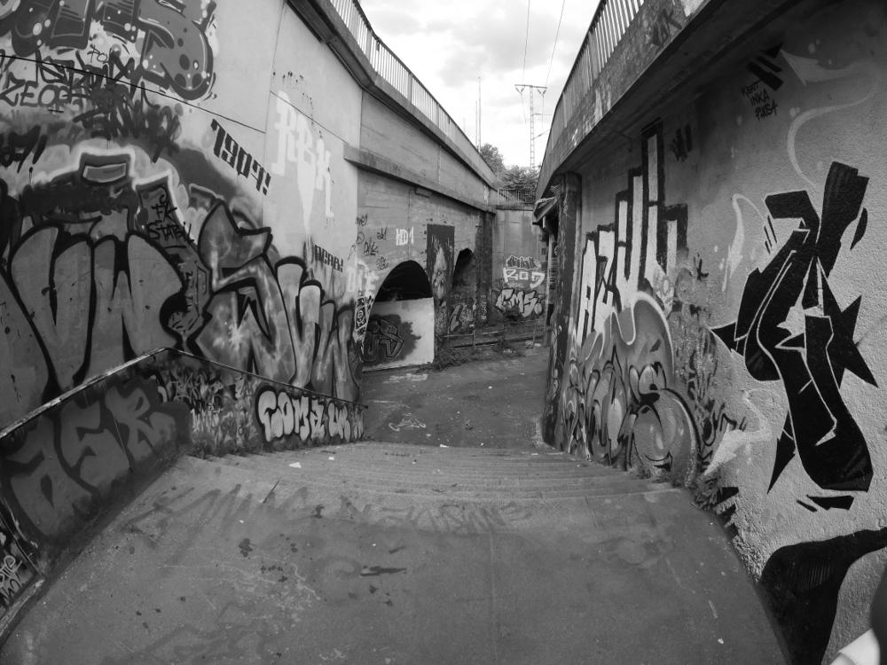 Das schwarz-weiß-Foto zeigt eine Treppe, die zwischen zwei Eisenbahnbrücken zu einer Fußgänger-Unterführung führt. Beide Seiten und auch die Tunnel der Unterführung sind mit verschiedenen Graffiti bemalt.