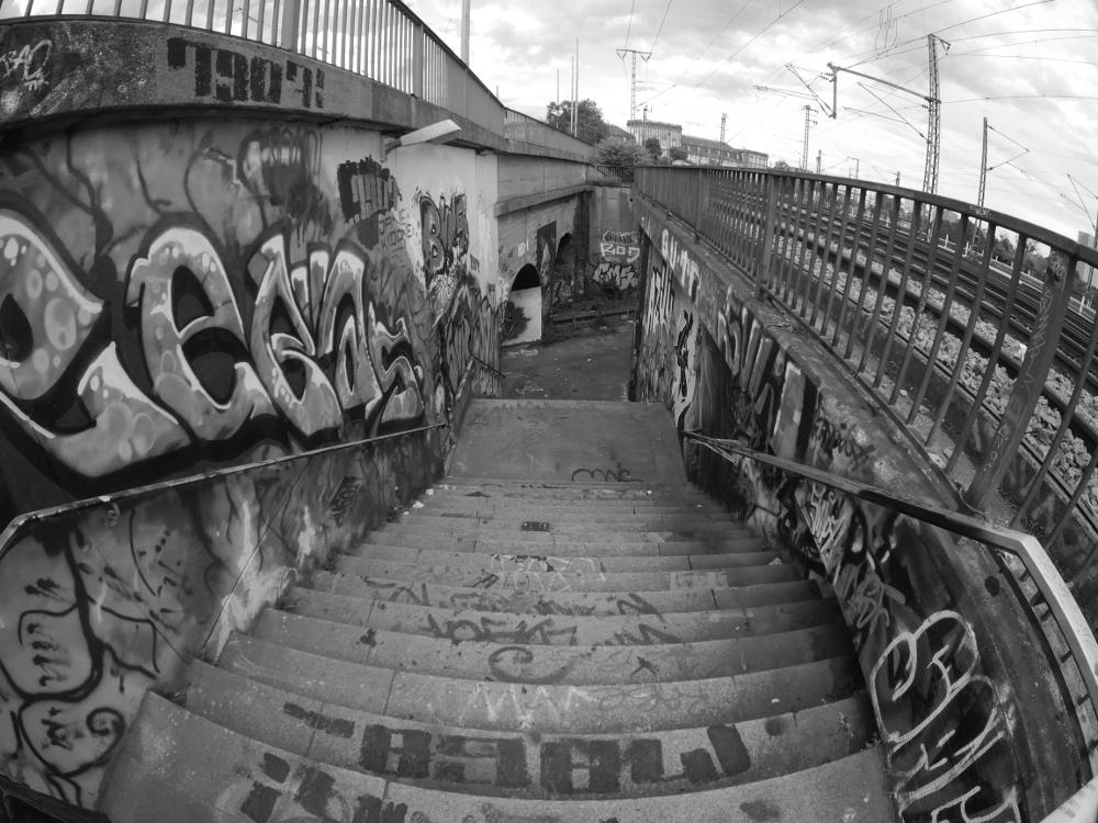 Das schwarz-weiß-Foto zeigt von der ebene der Schienen eine Treppe, die zwischen zwei Eisenbahnbrücken zu einer Fußgängerunterführung führt. Wände und auch etliche Treppenstufen sind mit Graffiti bemalt.