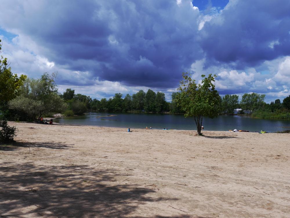 Eine Landschaftsaufnahme an einem ziemlich leeren Sandstrand an einem See. Am Himmel sind schon bedrohliche Regenwolken.