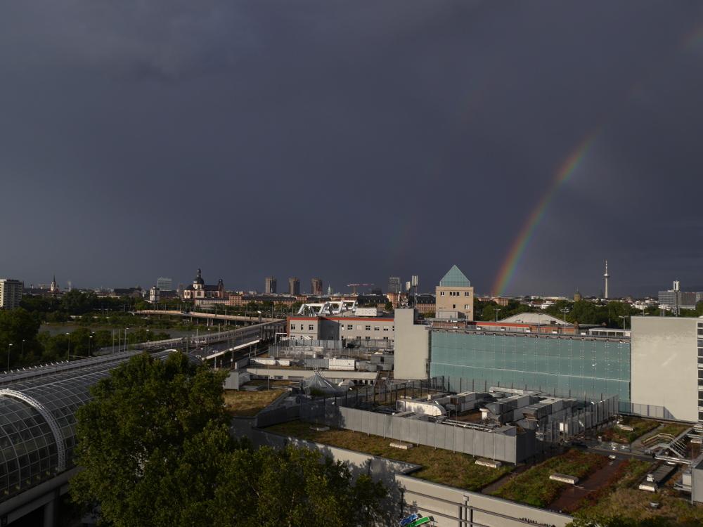 Eine Landschaftsaufnahme der Stadt Mannheim, am Mannheimer Schloß im rechten Drittel des Bildes beginnt ein Regenbogen, rechts ist der Fernsehturm von Mannheim zu sehen, Links Kirchen und davor die 3 Hochhäuser am Neckarufer.
