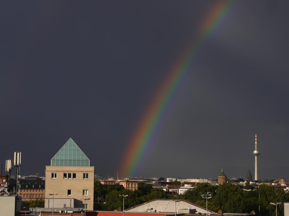 Ein Regenbogen über Mannheim, man sieht den Regenbogen ungeführ am Stadtschloß beginnen und er geht nach oben weg, rechts im Bild ist der Fernsehturm