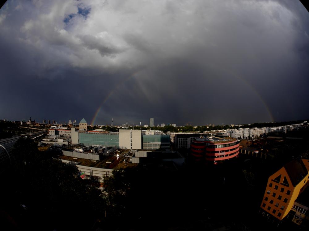 Eine Panoramaaufnahme mit einem Fischaugen-Objektiv, das Bild ist dadurch verzerrt. Man sieht den ganzen Regenbogen über der Stadt Mannheim und im ordergrund noch einen Teil von Ludwigshafen mit der Walzmühlen-Einkaufszentrum und dem Lusaneum-Arzthaus