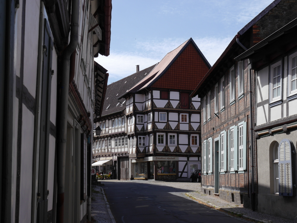 Das Foto zeigt eine kleine Straße, Rechts und LInks stehen Fachwerkhäuser. Es gibt eine Einmündung und die Straße macht einen Bogen, dort sieht man Geschäfte.