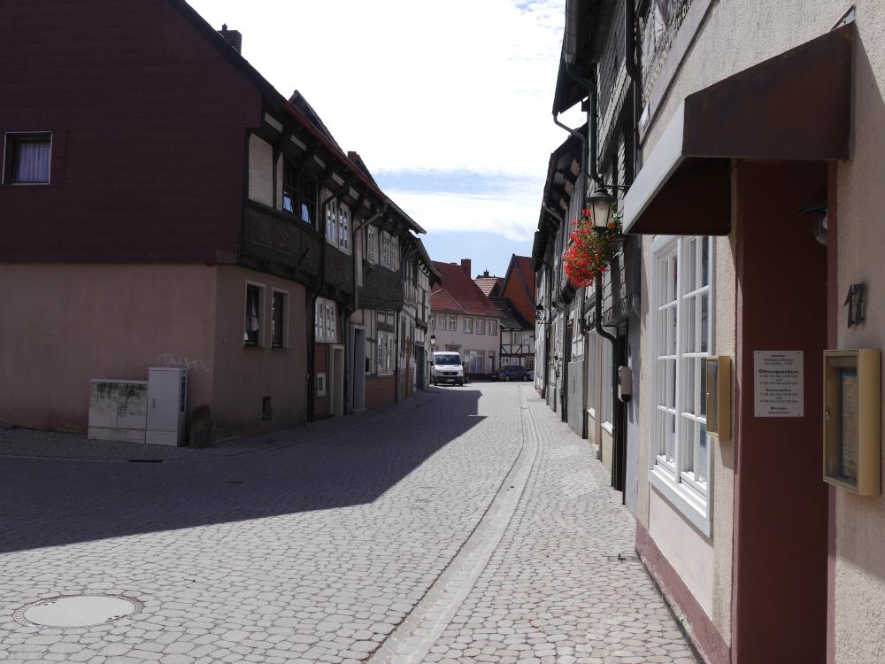 Blick entlang einer kleinen Kopfsteinflaster-Straße, Rechts und LInks stehen Fachwerkhäuser. An einem der Häuser rechts sind am Obergeschoß Blumenkästen mit Roten Blumen angebracht, weiter hinten steht ein Kleintransporter.