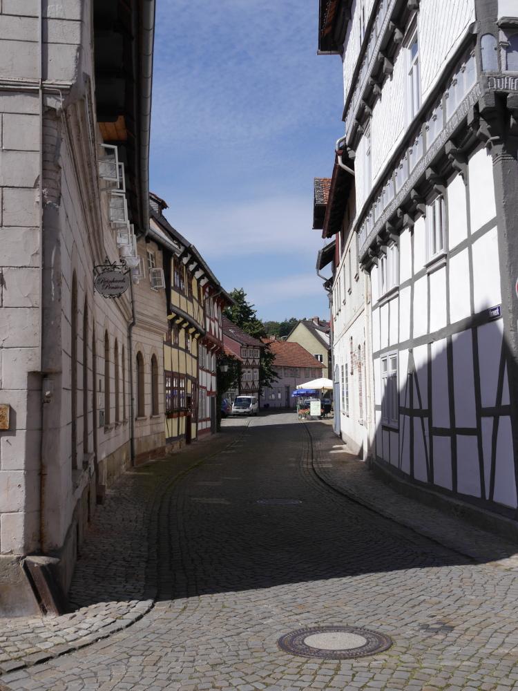 Blick von einer Einmündung auf eine kleine, von Fachwerkhäusern und anderen alten Häusern gesäumte Straße. Man sieht die Sonnenschirme eines Straßen-Restaurants.