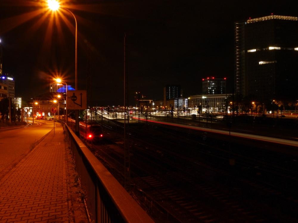 Das Foto zeigt eine Nachtaufnahme bei Dunkelheit des Hauptbahnhofs von Mannheim, durch den Bahnhof führt ein Weiß-/Roter-Lichtstreifen von einem einfahrenden ICE.