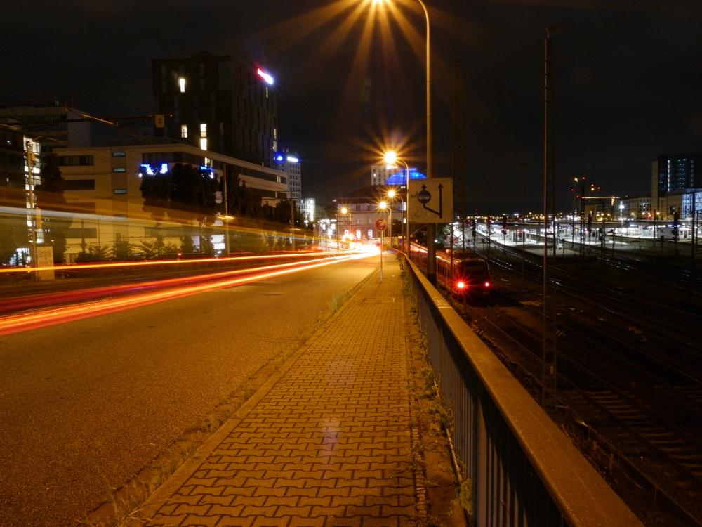 Eine Nachtaufnahme an einer Straße neben dem Mannheimer Hauptbahnhof. Rechts ist das dunkele Gleisfeld und die erleuchteten Bahnsteige zu erkennen, links der Straße verlaufen Straßenbanschienen und man kann die Lichtspuren von durchfahrenden Bahnen erkennen.