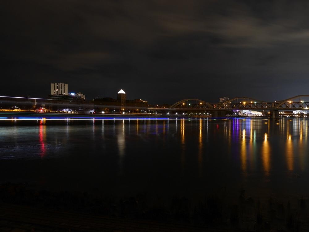 Eine Nachtaufnahme des Rheins in Mannheim. Die Aufnahme ist in Richtung Ludwigshafen, man erkennt die Rheinbrücke, dahinter die erleuchtete Spitze der Walzmühle und ein Hochhaus. Auf dem Wasser sind durch ein durchfahrendes Binnenschiff blaue und weiße Lichtstreifen erkennbar.