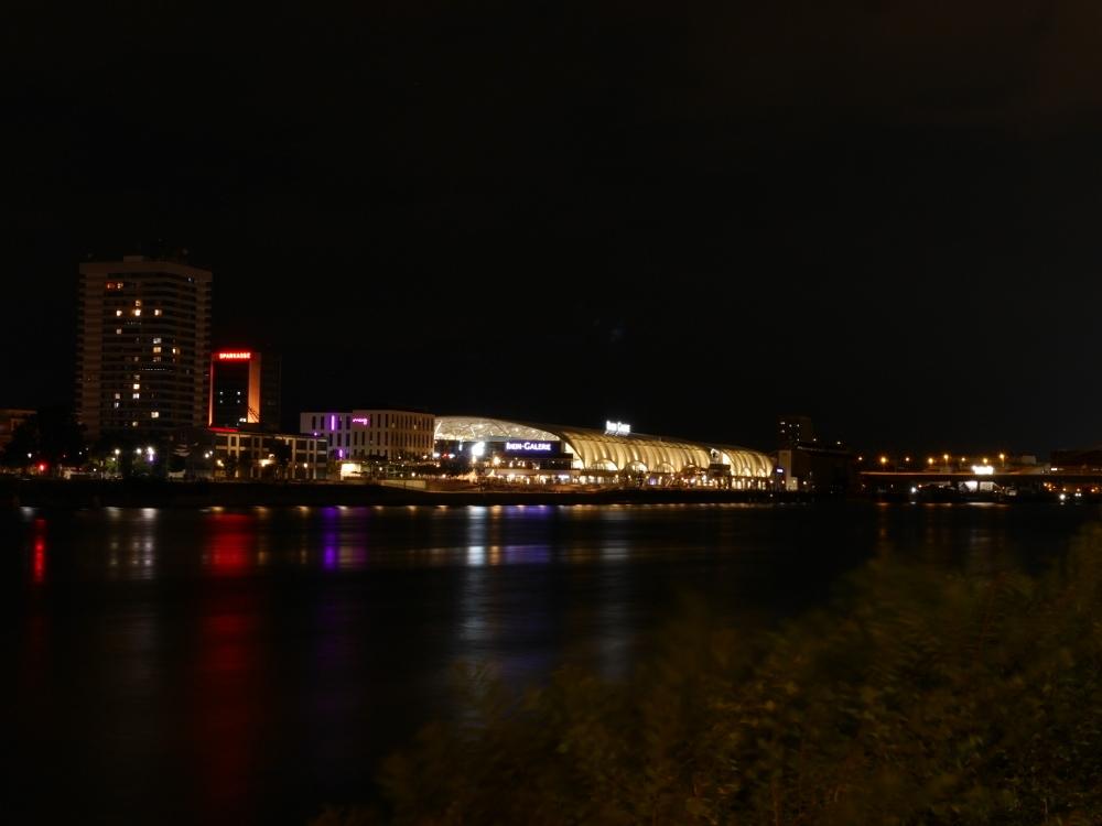 """Eine Nachtaufnahme des Einkaufszentrums """"Rhein-Galerie"""" und der umstehenden Häuse in Ludwigshafen, die Aufnahme ist auf der anderen Rhein-Seite in Mannheim entstanden."""