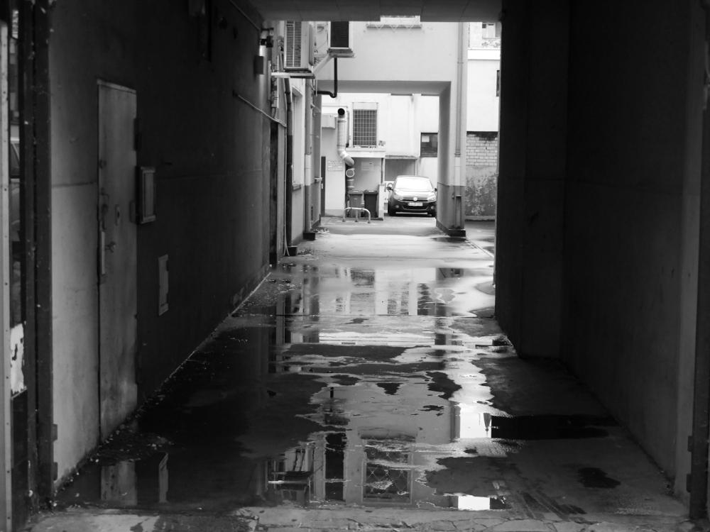 Ein schwarz-weiß-Foto von einer Durchfahrt zu einem Hinterhof. Es hat kürzlich geregnet und auf der Einfahrt und dahinter auf dem Hof sind große Pfützen, in denen sich die Höuser spiegeln. Weiter hinten ist ein Auto erkennbar. Es wirkt alles etwas heruntergekommen.