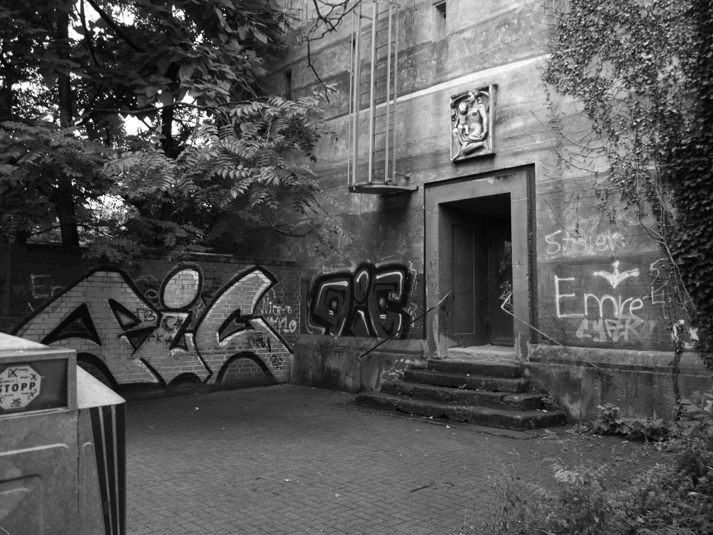 Ein schwarz-weiß-Foto. Das Foto zeigt eine leicht verdreckte und mit Graffiti beschmierte Ecke an einem alten Bunktereingang, am linken Bildrand ist ein Altglascontainer erkennbar.