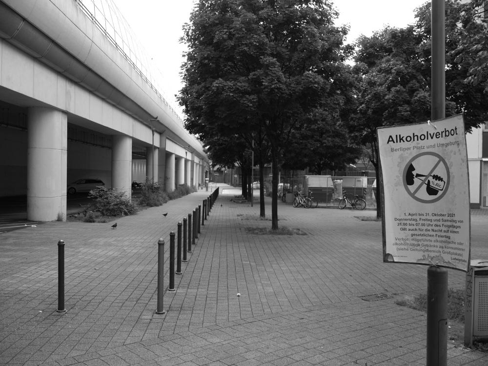 Ein s/w-Foto eines leeren Fußwegs an einer Eisenbahnbrücke. Unter der Brücke sind Parkplätze und durch ds Bild zieht sich auch eine Reihe Poller. Auf der rechten Bildseite hängt ein Plakat zum Alkoholverbot in diesem Bereich (Berliner Platz in Ludwigshafen),. Es ist MEnschenleer