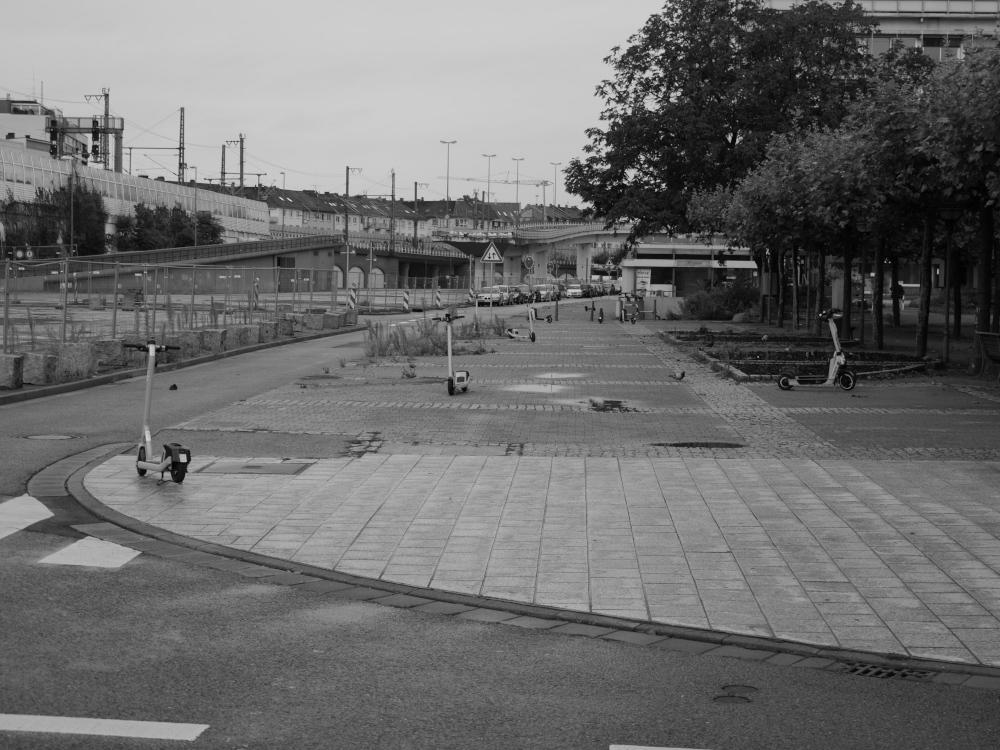 Ds s/w-Foto zeigt den menschenleeren Fußweg am sog. Plantanenhain in der Innenstadt von Ludwigshafen, links daneben der abgerissene Teil der Hochstraße und daneben die Bahnstrecke. Auf dem großen Fußweg stehen kreuz und quer etwa ein halbes Dutzend von diesen Elektro-Tretrollern, dazwischen sind Tauben. Man sieht Pfützen vom Regen.