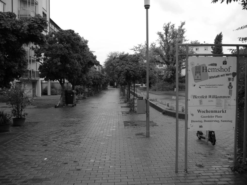 """Ein s/w-Foto aus der Innenstadt von Ludwigshafen. Es ist regnerisch und menschenleer. Rechts ein Schild """"Hemshof, Altstadt mit Herz"""". Davon geht eine großer Fußweg mit Bäumen ab, immer mal wieder sieht man abgestellte Elektro-Tretroller, Prüftzen usw."""