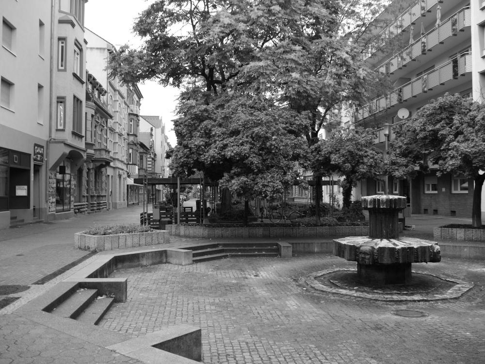 Das s/w-Foto zeigt einen menschenleeren Platz in der Fußgängerzone in Ludwigshafen-Hemshof, die Geschäfte sind geschlossen, und ein paar Stufen führen runter zu einem älteren Spreingbrunnen, der aber auch ausgeschaltet ist.
