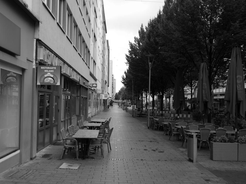 Ds s/w-Foto ist ein Blick entlang der großen Straße der Fußgängerzone in der Innenstadt von Ludwigshafen. LIn ks am Bildanfang ist ein italienisches Restaurant, welches Tische auf der Straße hat, dahinter eine Baustelle. Es ist regnerisch und menschenleer.