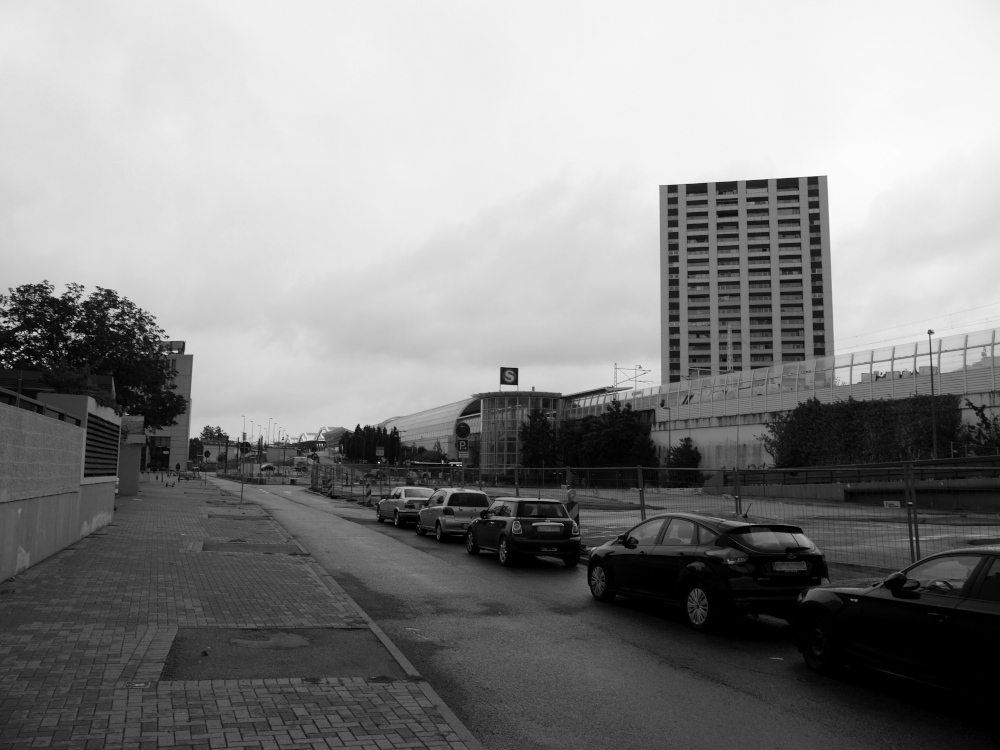 Ein s/w-Foto im Zentrum von Ludwigshafen, aufgenommen an der abgerissenen Hochstraße. Man sieht den S-Bahnhof Ludwigshafen Mitte und daneben das Yorkhaus auf der rechten Seite, Links den Weg zum Berliner Platz und zum Faktorhaus. Rechts am Straßenrand der Bauzaun und davor diverse Autos. Es ist menschenleer.