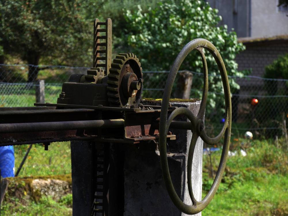 Das Foto zeigt ein Handrad und einen Teil von Getriebe von einem alten Wehr in einem Bach, es ist alles verrostet und bemost.