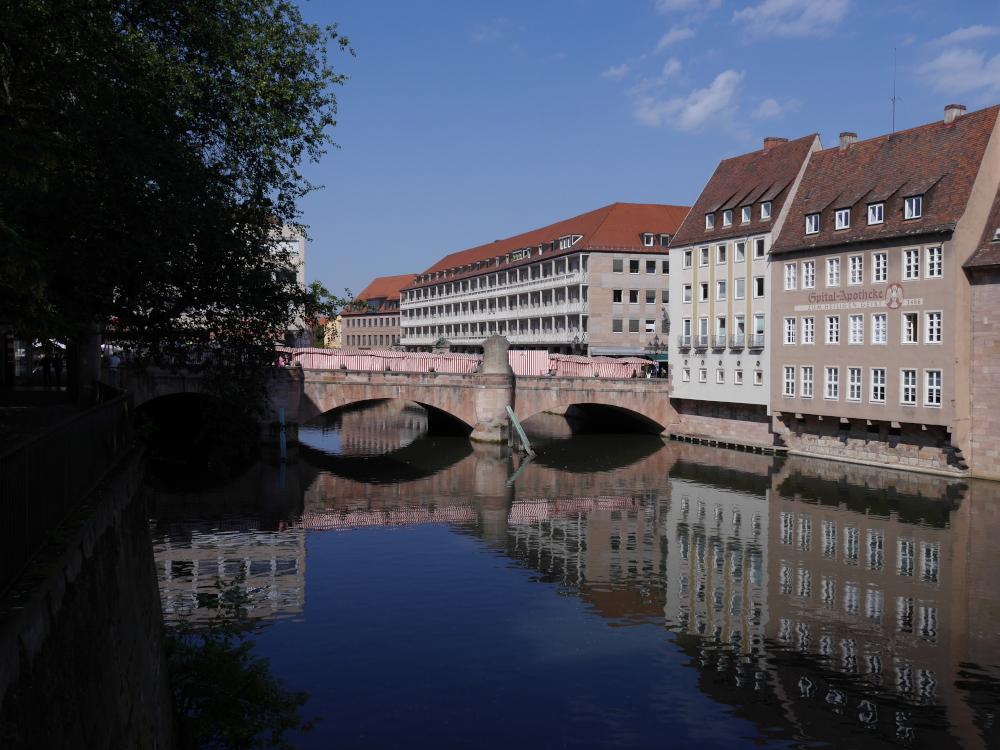 """Das Foto zeigt eine Stadtaufnahme an der Pegnitz, man sieht eine Brücke die etwa in der Mitte des Bildes über den Fluß geht, Rechts sind Häuser unmittelbar am Ufer und spiegeln sich im relativ stillen Wasser. Auf einem der Häuser steht """"Spital-Apotheke""""."""